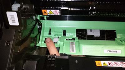 фото. Палец наживаем датчик сброса тонера в принтере. DR-1075